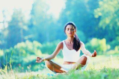 Fotomural Mulher nova que faz exercícios de ioga no parque verde
