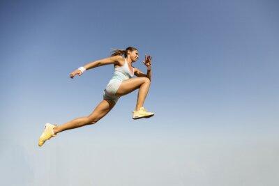 Fotomural Mulher nova que toma salto em comprimento