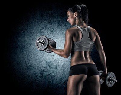 Fotomural Muscular woman in studio on dark background