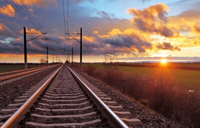 Fotomural Orange sunset in low clouds over railroad