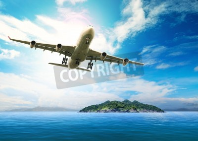 Fotomural passenger plane flying over beautiful blue ocean and island in purity destination sea beach use for summer holiday vacation treveling