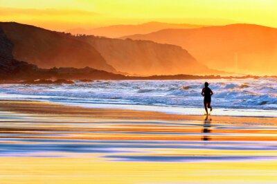Fotomural pessoa correndo na praia ao pôr do sol
