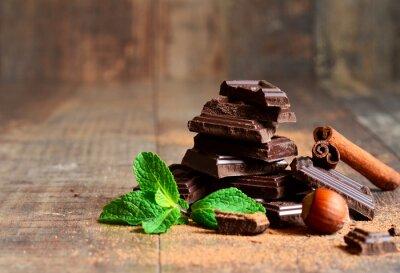 Fotomural Pilha de fatias de chocolate com folha de hortelã, avelã e canela.