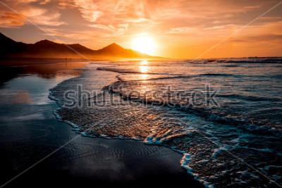 Fotomural Pôr do sol incrível praia com horizonte infinito e figuras solitárias à distância e incríveis ondas de espuma. Colinas vulcânicas no fundo em cores mornas idílicas.