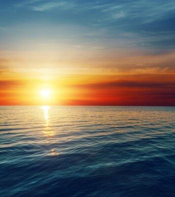Fotomural por do sol vermelho sobre a água escura