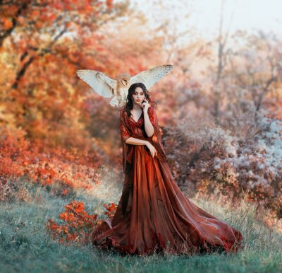 Fotomural pretty young girl with black hair in cold forest, orange foliage of trees, fairy of autumn season in long red burgundy vintage dress with chic train, lady with white owl on shoulder, bloody sorceress