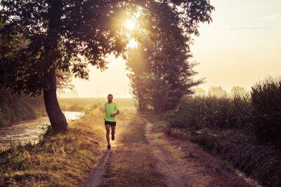 Fotomural Ragazzo che corre all'alba su strada de campo na propriedade