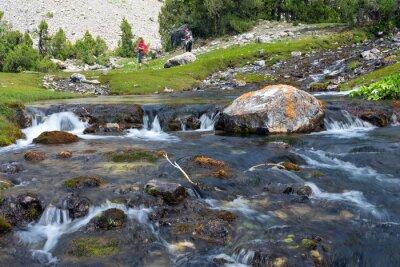 Fotomural Rápida e ampla cascata rio movente rápido vívido água pedras rochosas e grupo de pessoas que anda no prado verde no fundo
