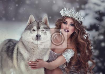 Fotomural Retrato de mulher de vestido prata e coroa como rainha da neve, na floresta de inverno com cães Husky. A princesa fada e o lobo no inverno.