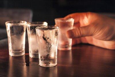 Fotomural Tiro copo de vodka na mão em uma mesa de madeira.