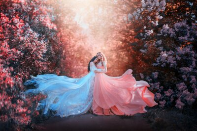 Fotomural two women in long dresses hugging train flies wind. bright fabulous purple colors art retouching processing. Natural cosmetics scented spring flowers tenderness smell perfume. Blonde brunette hair