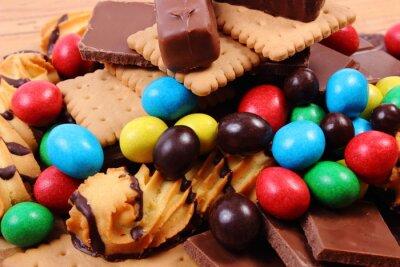 Fotomural Um monte de doces na superfície de madeira, alimentos insalubres