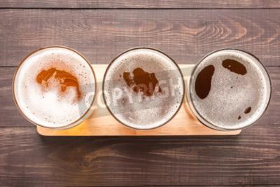 Fotomural Variedade de copos de cerveja em um fundo de madeira. Vista superior.