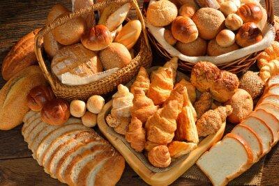 Fotomural Variedade de pão na cesta de vime no fundo de madeira velho.