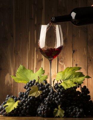 Fotomural Vidro com vinho tinto e grapeson a mesa de madeira
