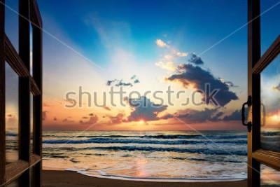 Fotomural Vista do nascer do sol sobre o mar da janela aberta
