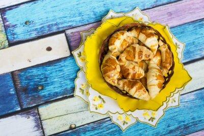 Fotomural Самодельные круассаны в плетеной корзинке на желтой салфетке с цветочным узором на старом / вытертом полу