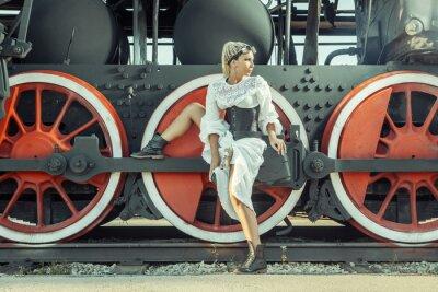 Poster A mulher no vestido do vintage está sentando-se na roda da locomotiva.