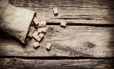 Poster Açúcar de cana refinado no saco. No fundo de madeira.