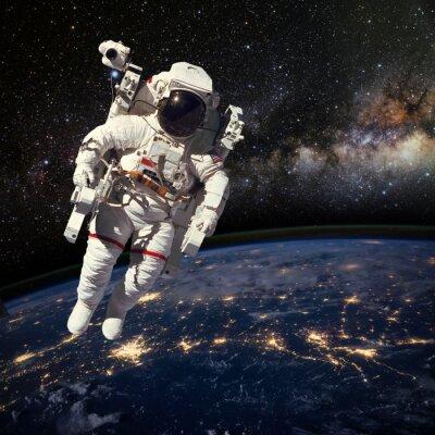 Poster Astronauta no espaço acima da terra durante o período nocturno. Elem