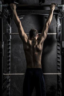 Poster Bodybuilding, homem forte novo atlético que mostra os músculos das costas trabalhando em Educação Física Bar, contraste forte com filtro Saturado Grunge