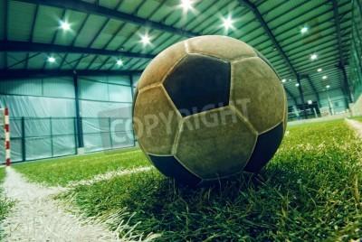 Poster bola de futebol na grama verde em um playground indoor