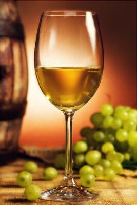 Poster Copo de vinho branco na frente de uvas verdes e velho barril