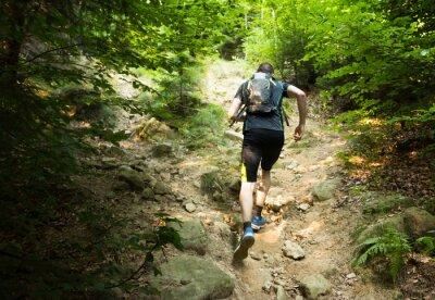 Poster corredor da fuga com a mochila correndo a colina íngreme