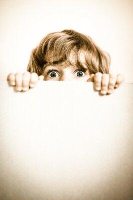 Poster Criança que olha por trás do papel em branco