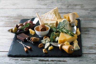 Poster Delicioso queijos em uma placa com mel, nozes em um backgro branco