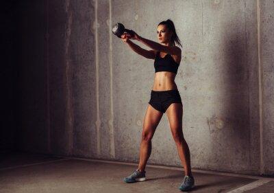 Poster Desportista esbelta e atraente em um treinamento kettlebell