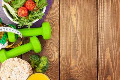 Poster Dumbells, fita métrica e alimentação saudável sobre a tabela de madeira