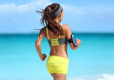 Poster Executando a motivação - treinamento do corredor com a música vista de trás que movimenta-se na forma amarra correias sutiã dos esportes e equipamento dos shorts de néon que desgasta fones de ouvido s