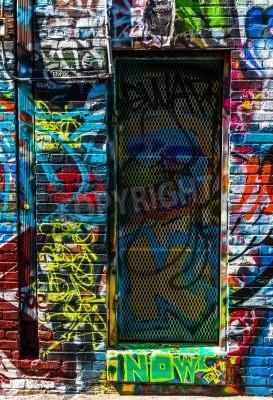Poster Graffiti nas paredes e porta em Graffiti Alley, Baltimore, Maryland.