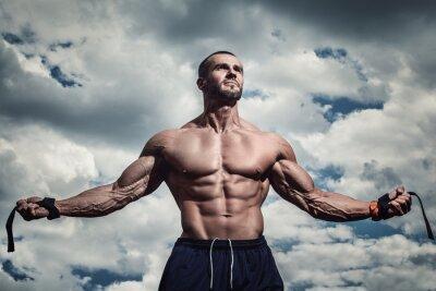 Poster Homem muscular sob o céu nebuloso