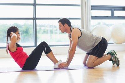 Poster Instrutor que ajuda a mulher fazer flexões abdominais em ginásio