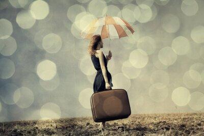 Poster Menina do Redhead com guarda-chuva e mala no campo ventoso