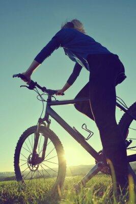 Poster Menina em uma bicicleta no por do sol