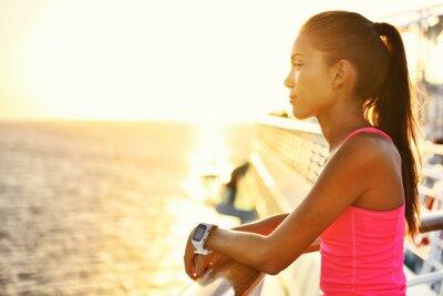 Poster Mulher ativa que relaxa após o funcionamento no navio de cruzeiros que olha o mar durante férias de verão. Asiático, corredor, menina, Desgastar, smartwatch, Coração, taxa, atividade ...