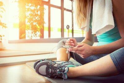 Poster Mulher loura atrativa com telefone inteligente, que descansa após treino de ginástica