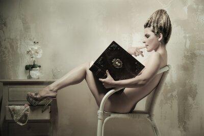 Poster Mulher nua sentada em uma cadeira lendo um livro dentro de casa