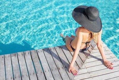Poster Mulher sentada no deck à beira da piscina
