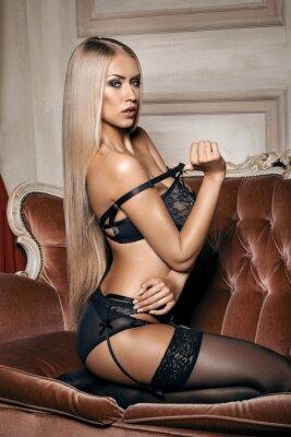 Poster Mulher sexy na roupa interior preta sedutora sentado em um sofá em meias