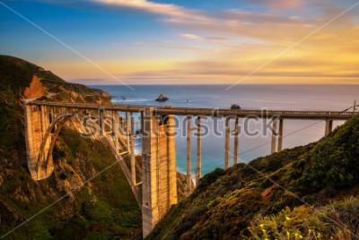 Poster Ponte de Bixby (ponte da angra rochosa) e estrada da Costa do Pacífico no por do sol perto de Big Sur em Califórnia, EUA. Exposição longa.