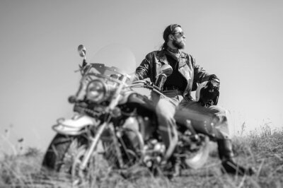 Poster Retrato de um homem novo com a barba que senta-se em sua motocicleta do cruzador e que olha ao sol. O homem está desgastando o revestimento de couro e calças de ganga. Baixo ponto de vista. Incline o