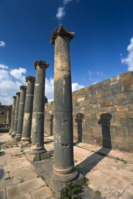 Poster Síria. Bosra. Os restos dos banhos romanos - colunas de basalto. Este site está na Lista do Património Mundial da UNESCO