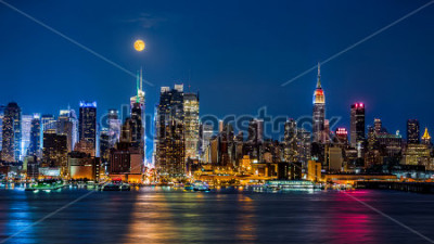 Poster Super Moon above New York skyline. The top of the Empire State Building is illuminated with the colors of the German and Argentinian flags in honor of the Soccer World Cup final.