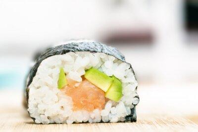 Poster Sushi com salmão, abacate, arroz em alga e pauzinhos na mesa de madeira