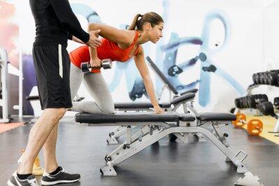 Poster Trainer masculino novo que dá instruções a uma mulher em um ginásio