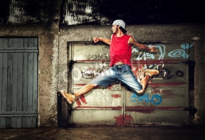 Poster Young man jumping / dancing on grunge graffiti wall background